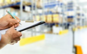 Man-Writing-on-Clipboard-in-Storage-Warehouse-in-Elk-Grove-Village-IL