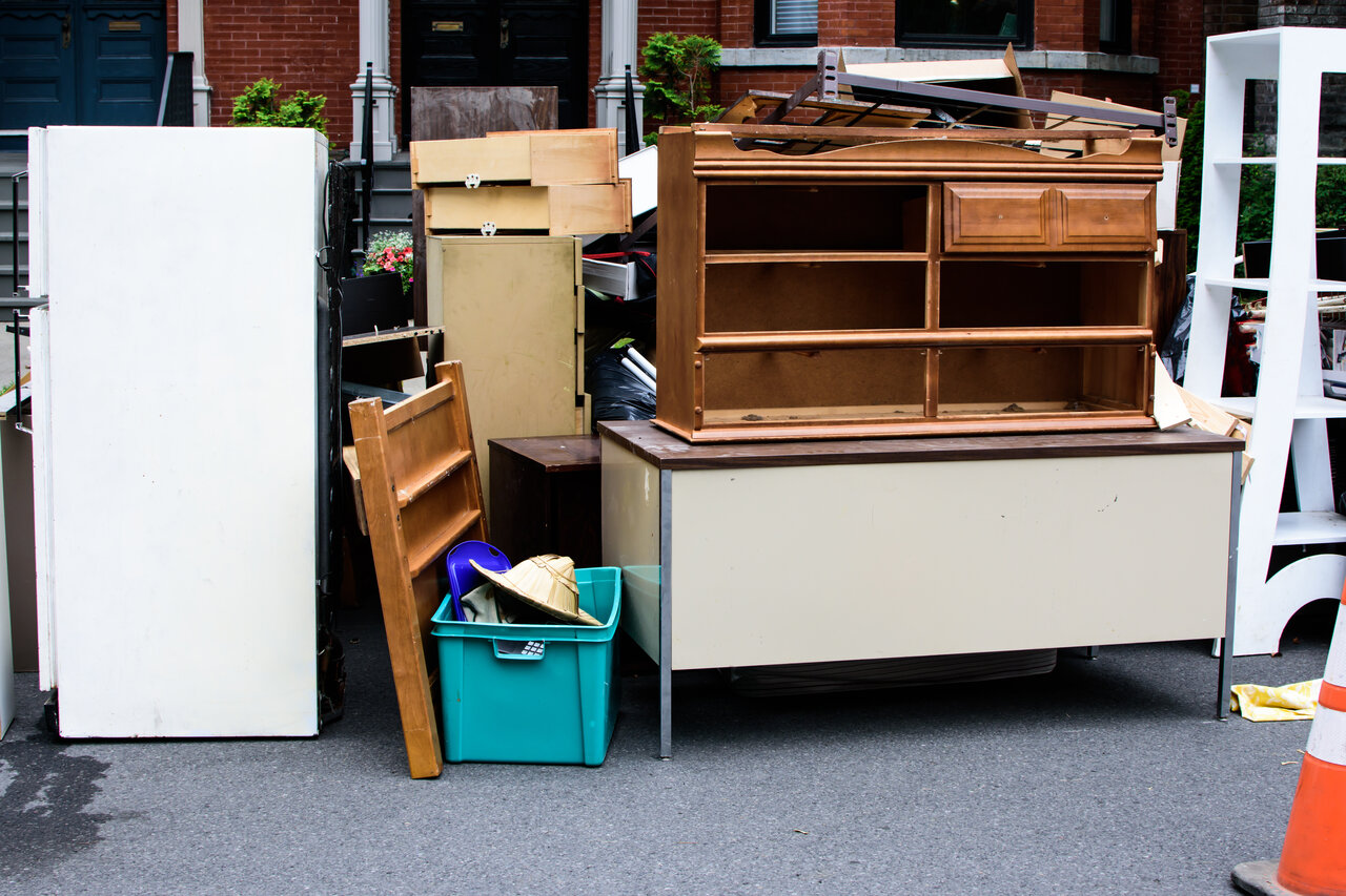 Items and old furniture on street outside house moving day or getting rid of junk concept